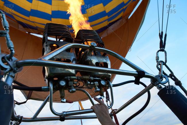 Man inflating hot air balloon with gas burner