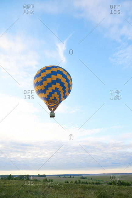 Single hot air balloon floating over the field