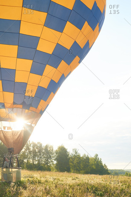 Man soaring in his hot air balloon amid the field