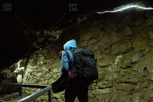 Tourist with backpack exploring a cave in the Urals, Russia