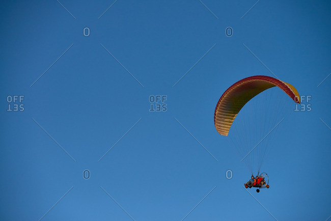 Two men driving powered paraglider