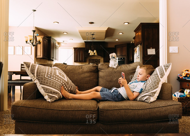 Boy lounging on sofa using phone