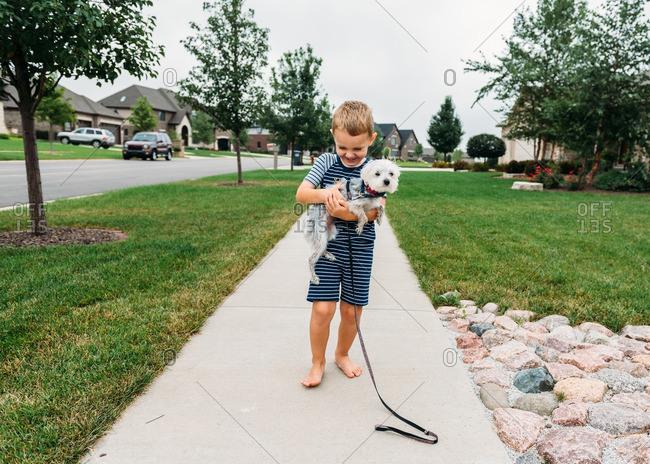 Boy carrying dog on sidewalk