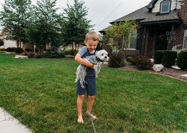 Boy in a yard holding dog