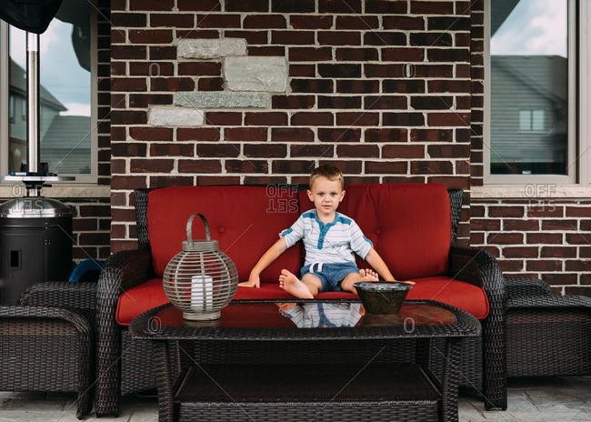 Boy on patio sofa outdoors