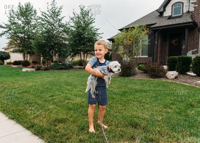 Boy in a yard holding a dog