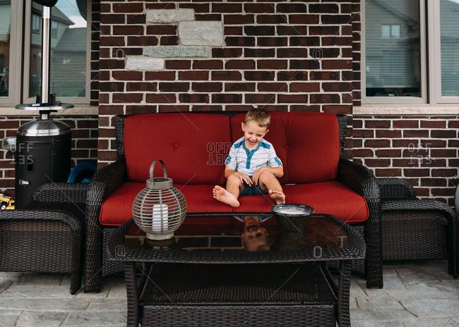 Boy laughing on patio sofa