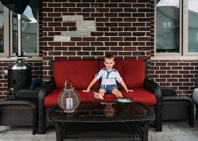Boy on a patio sofa outdoors