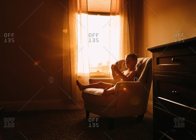 Boy in golden light in chair