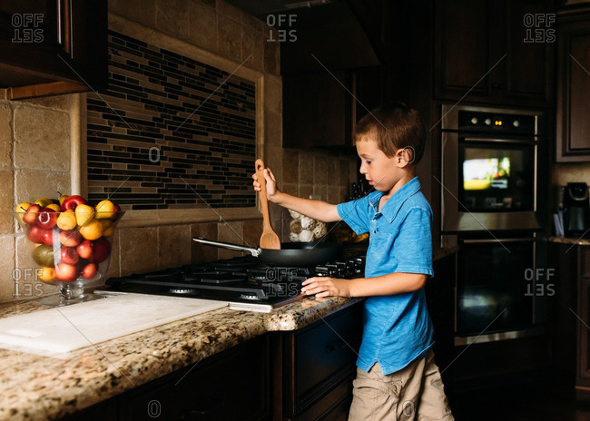 Boy cooking with a pan