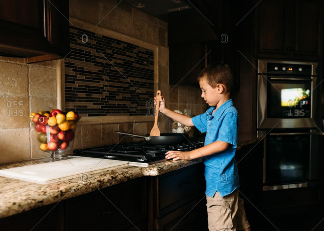 Boy cooking with a skillet