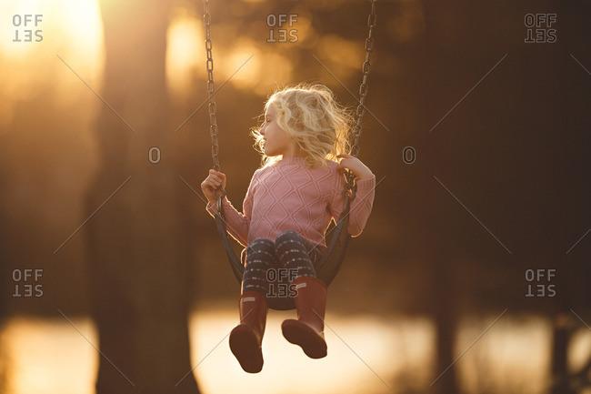 Girl swinging in late day sun