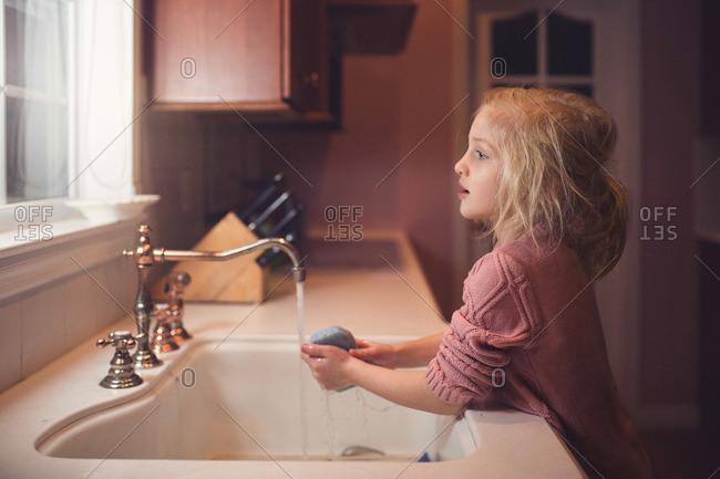 Girl washing up at kitchen sink