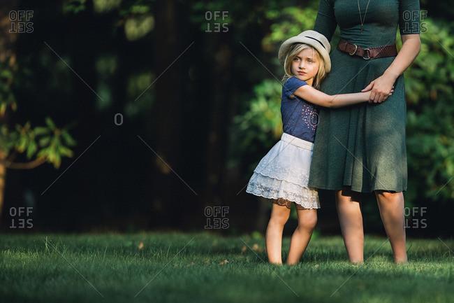 Girl hugging on woman in yard