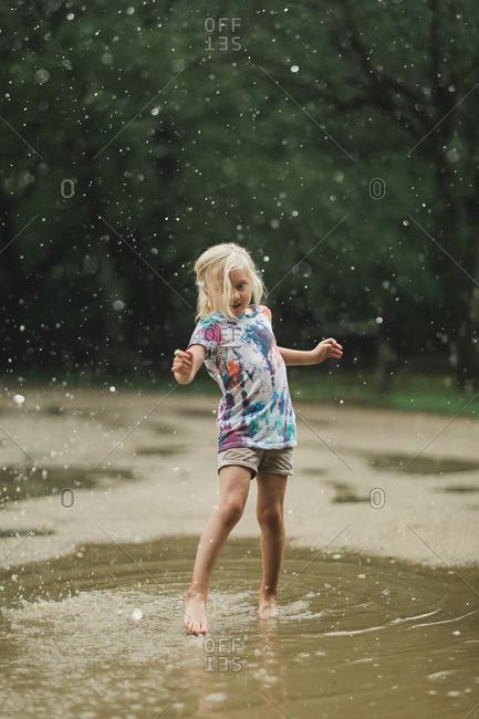 Girl splashing into a puddle