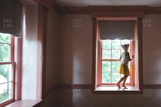 Girl standing in window looking out