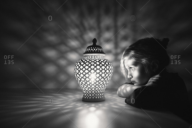 Girl by lamp making shadow patterns