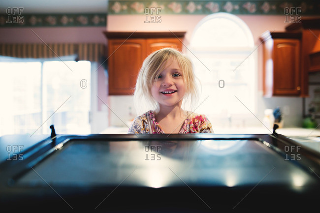Girl in kitchen smiling happily