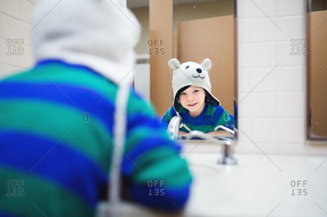 Boy in hat at bathroom sink