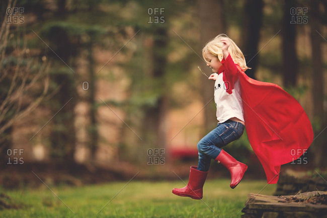 Girl in cape and boots leaping