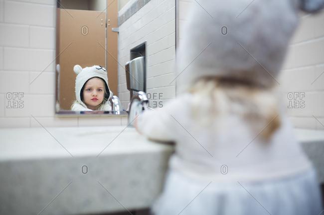 Girl in hat at bathroom sink