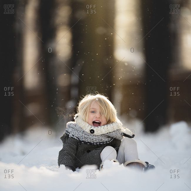Smiling girl sitting in snow
