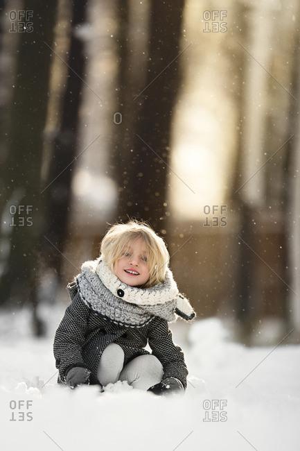 Girl smiling sitting in snow