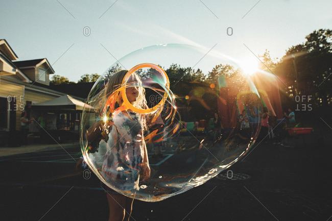 Girl making bubbles in street