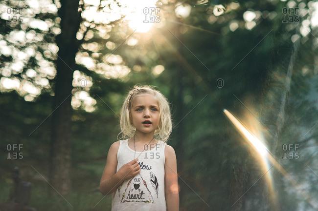 Girl in tank top in sunlit woods