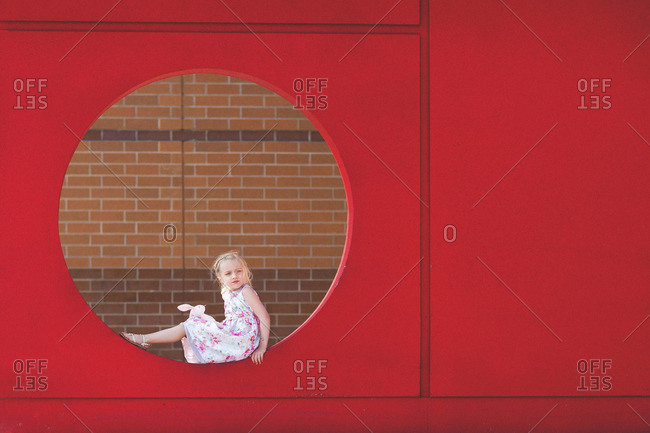Girl sitting in circle hole in wall