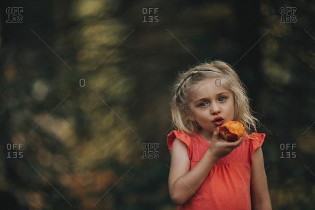 Blonde girl eating fruit outside