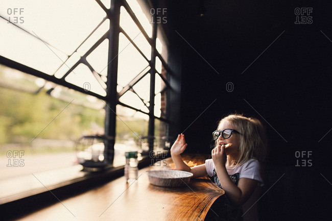 Girl in restaurant waving out window