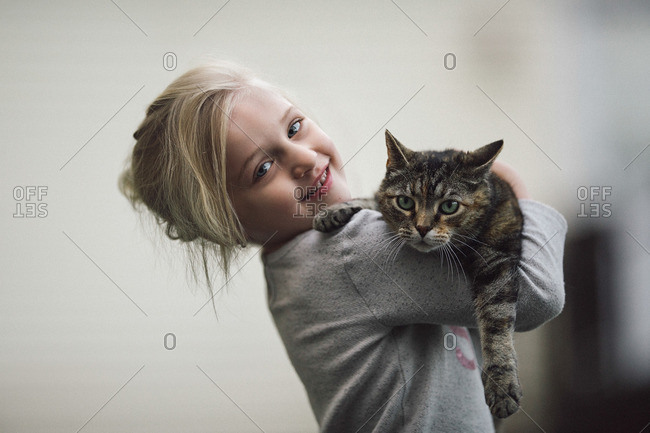 Girl holding up cat inside home