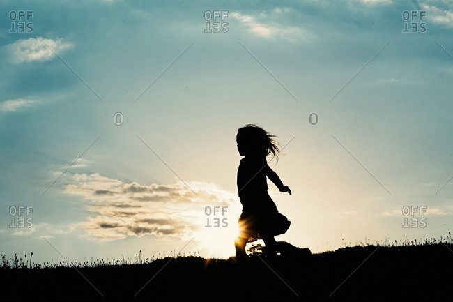 Girl in silhouette on hill