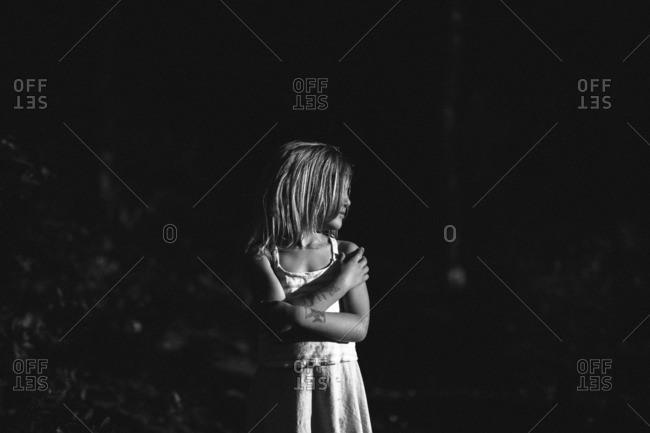 Girl in woods hugging herself