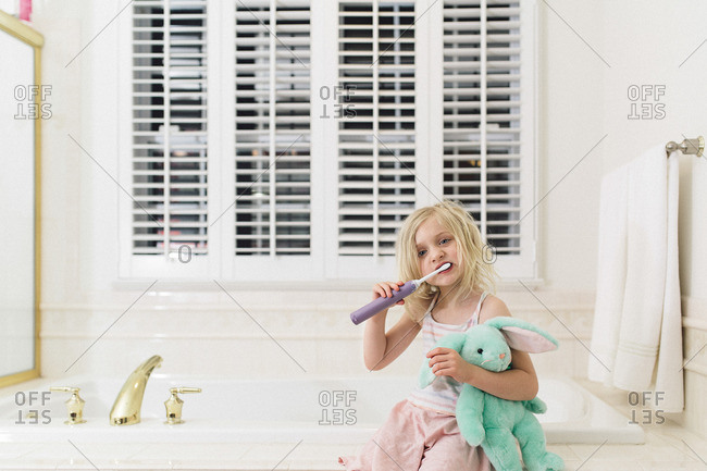 Girl holding doll brushing teeth