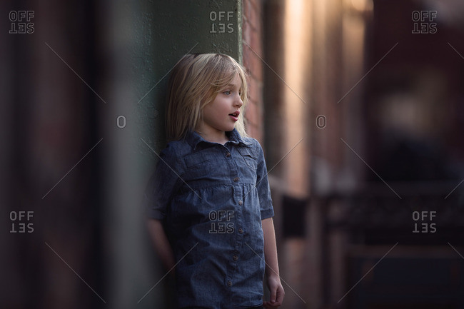 Girl leaning against wall at dusk