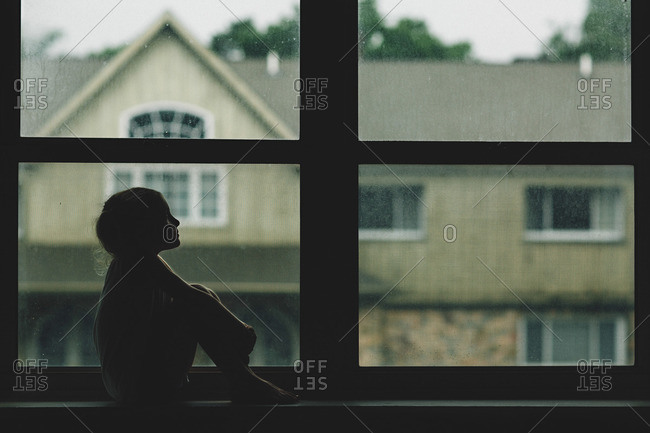 Girl silhouetted sitting in window