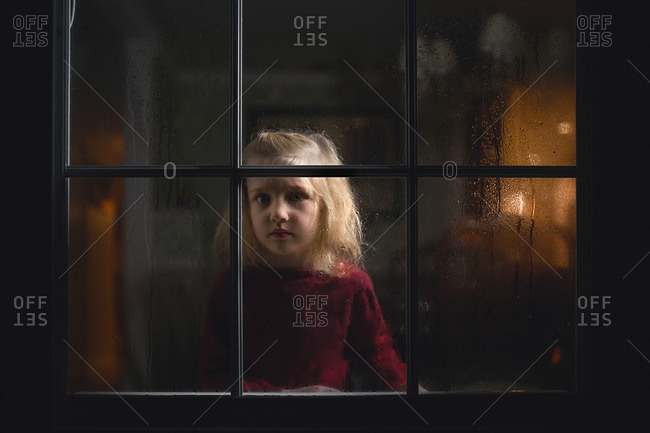 Girl looking out rain covered window