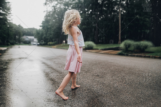 Girl standing in street in rain