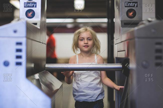 Girl by subway turnstiles