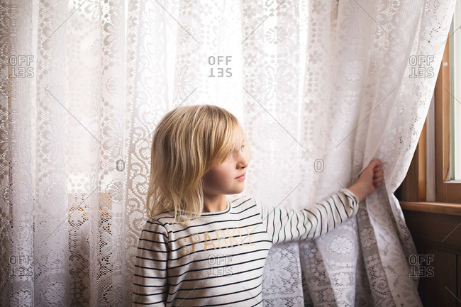 Girl staring out lace curtains