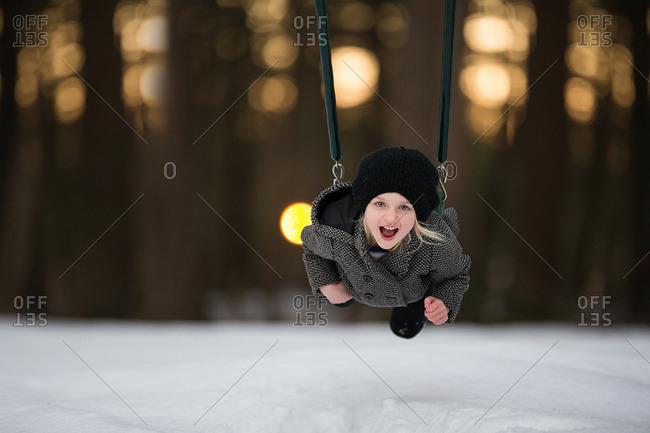 Girl on swing set in winter