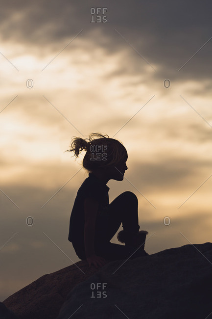 Girl sitting in silhouette at dusk