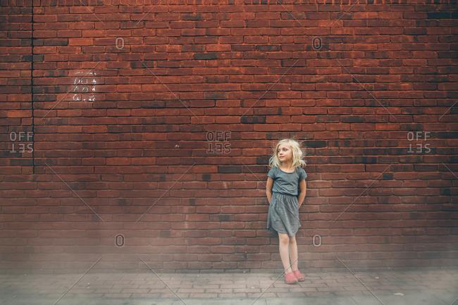 Girl by brick wall in fog