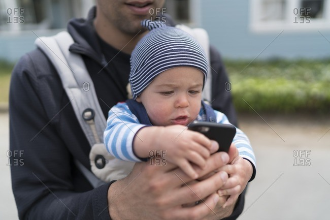 7 month old baby boy playing with his father's smartphone