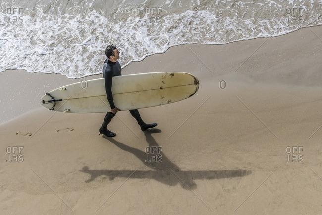 Surfer carrying his surfboard near Santa Cruz, California