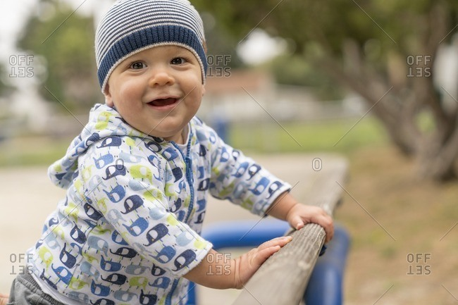 10 month old baby boy pulling himself up on a park bench