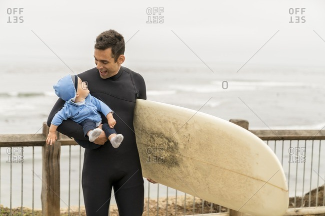 10 month old baby boy being held by his surfer father