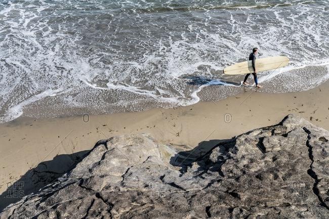 Surfer walks along the beach near Santa Cruz, California